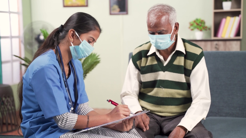 Young doctor or nurse writing prescription during home visiting to sick elder man while both worn face mask due to coronavirus covid-19 pandemic Royalty-Free Stock Footage #1063701064