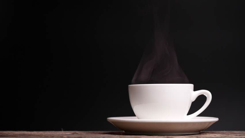 Coffee cup with natural steam smoke of coffee on dark background with copy space, slow motion. Hot Coffee Drink Concept. Royalty-Free Stock Footage #1063713238