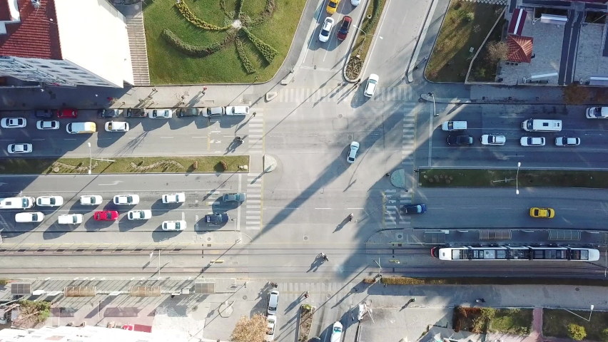 Aerial view of the city traffics at the center. Vehicles are moving on the road between buildings.