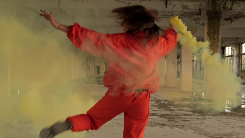 Stylish woman with smoke in hand dancing in abandoned factory. Freestyle dance improvisation. Young carefree woman in orange wear enjoys dancing in 4K, UHD
