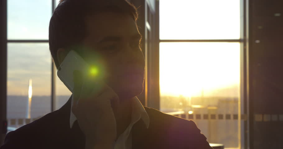 Young businessman talking on cell phone at the airport by the window with sunset view #10637180