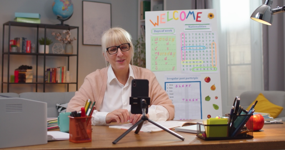 Good-looking Caucasian woman teaching students via video conference on smartphone at home. Adult female English teacher speaking on camera indoors. Education, e-learning, technology concept. Royalty-Free Stock Footage #1063727605