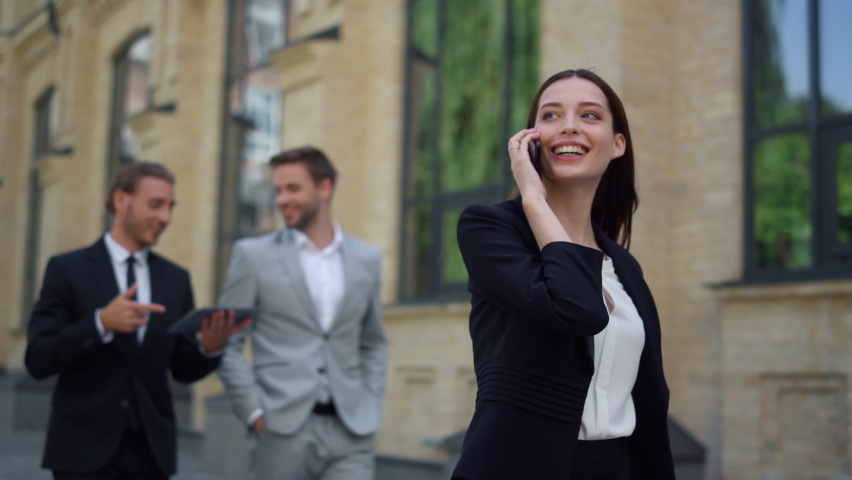 Business woman speaking mobile phone onthe go to office outdoors. Smiling business people using digital devices while walking on city street. Corporate people rushing to work outside. Royalty-Free Stock Footage #1063735822