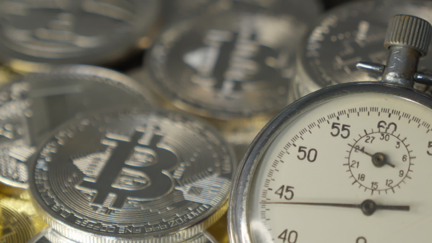 Silver Bitcoin and Analogue metal stopwatch. Close-up, macro shot. | Shutterstock HD Video #1063742365