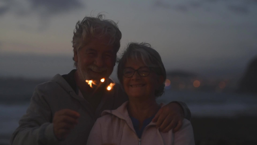 New year. close up of seniors celebrating the new year together at the beach with sparklers lights | Shutterstock HD Video #1063748518