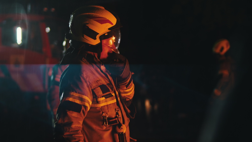 Close up of firefighter using radio to speak with his collegues. Fire engine with emergency lights and two more firemen in the background. High quality 4k footage Royalty-Free Stock Footage #1063750039