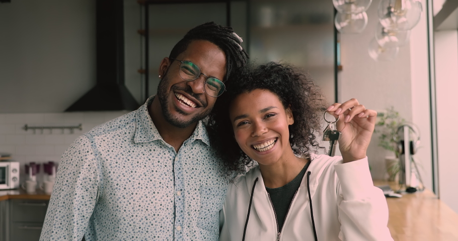 African couple standing in kitchen smile look at camera, happy wife show bunch of keys from new luxury house. Young family happy homeowners portrait, rented flat, loan mortgage, relocation day concept Royalty-Free Stock Footage #1063759651