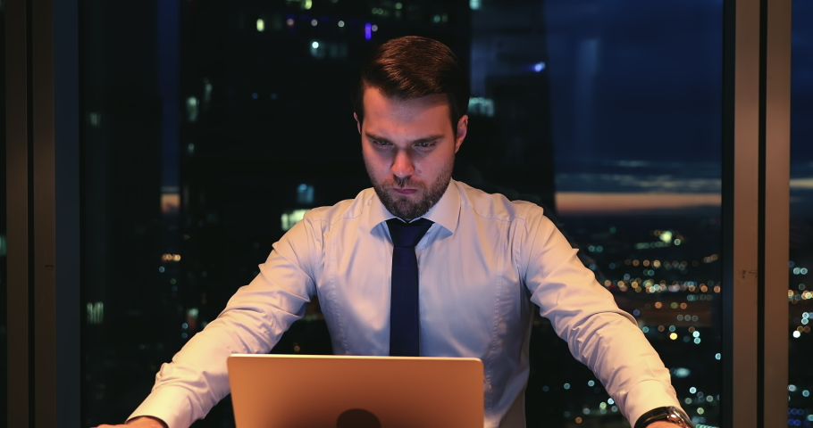 High-ranking official employee work until late in office room sit at workplace desk using laptop prepare report, develop project, solve business issues make urgent task, night city view through window Royalty-Free Stock Footage #1063765246