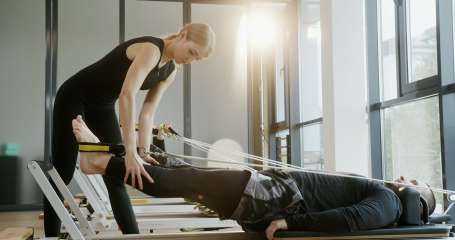 Rehabilitation after an injury the man is engaged in exercises for stretching of muscles of legs with the trainer on the newest exercise machine in sportswear in a sports hall | Shutterstock HD Video #1063766488