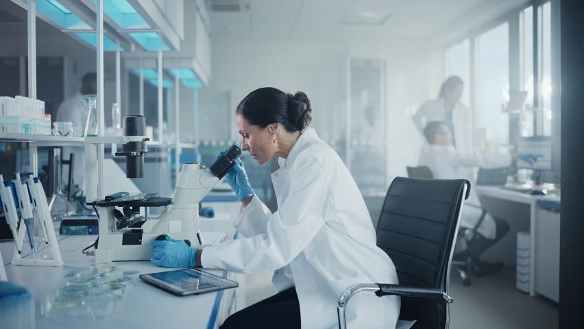 Medical Development Laboratory: Portrait of Beautiful Caucasian Female Scientist Looking Under Microscope, Analyzes Petri Dish Sample. People do Medicine, Biotechnology Research in Advanced Lab   Shutterstock HD Video #1063773001