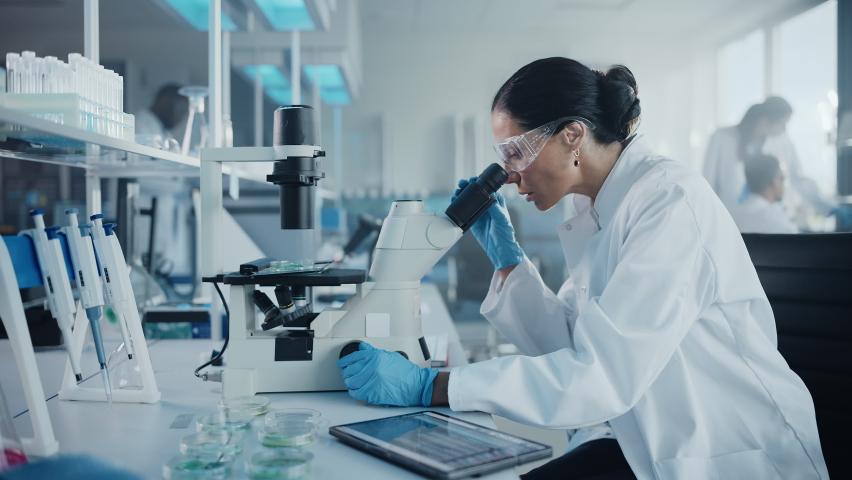 Medical Development Laboratory: Portrait of Beautiful Caucasian Female Scientist Looking Under Microscope, Analyzes Petri Dish Sample. People do Medicine, Biotechnology Research in Advanced Lab