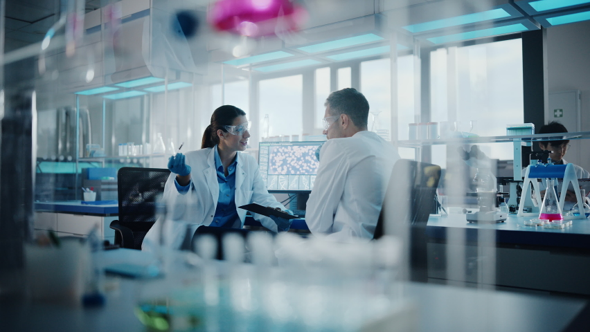 Modern Medical Research Laboratory: Portrait of Two Scientists Working, Using Digital Tablet, Analyzing Samples, Talking. Advanced Scientific Pharmaceutical Lab for Medicine, Biotechnology Development   Shutterstock HD Video #1063773190