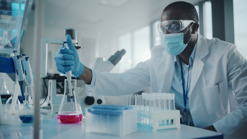 Medical Development Laboratory: Black Scientist wearing Face Mask Uses Pipette for Filling Test Tube with Liquid, Conducting Experiment. Pharmaceutical Lab with Medicine, Biotechnology Researchers Royalty-Free Stock Footage #1063773229