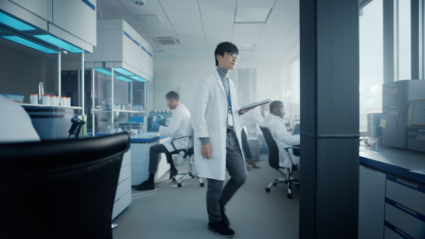 Medical Science Laboratory with Diverse Multi-Ethnic Team of Scientists Developing Drugs, Medicine, Doing Biotechnology Research. Working on Computer, Using Microscope, Analysing Samples. Slow Motion Royalty-Free Stock Footage #1063773241
