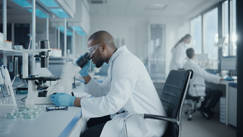 Medical Development Laboratory: Portrait of Black Male Scientist Looking Under Microscope, Analyzing Petri Dish Sample. Professionals Doing Research in Advanced Scientific Lab. Side View Static Shot   Shutterstock HD Video #1063773775