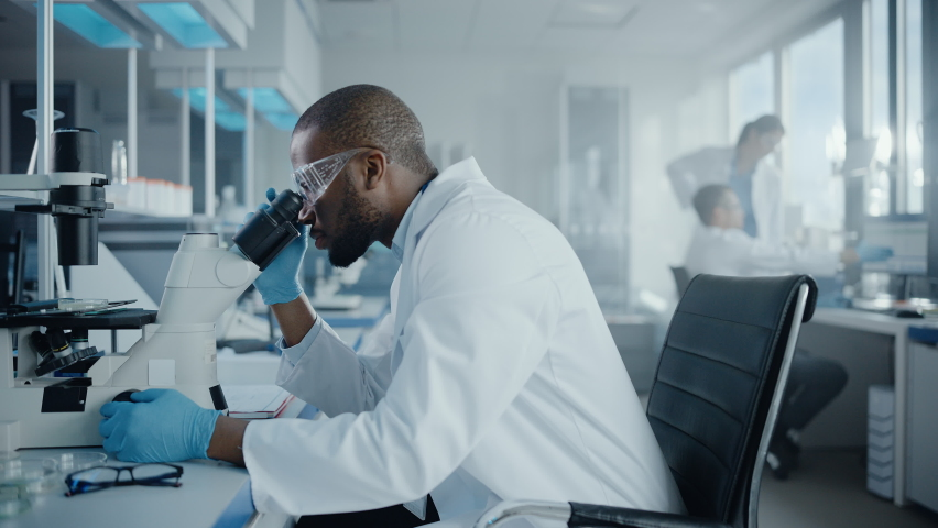 Medical Development Laboratory: Portrait of Black Male Scientist Looking Under Microscope, Analysing Petri Dish Sample. Professionals Doing Research in Advanced Scientific Lab. Side View Zoom In Shot   Shutterstock HD Video #1063773799