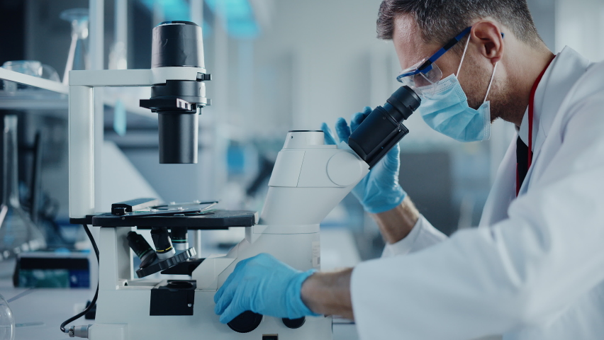 Medical Development Laboratory: Scientist Wearing Face Mask Uses Micro Pipette Dropper to Mix Petri Dish Sample. Specialists Working on Medicine, Biotechnology Research in Advanced Pharma Lab Royalty-Free Stock Footage #1063773826