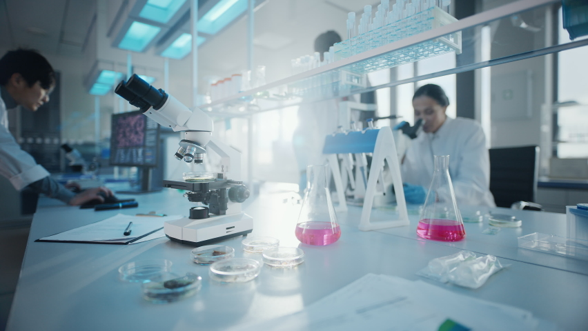 Medical Science Laboratory with Diverse Multi-Ethnic Team of Scientists Developing Drugs, Medicine, Doing Biotechnology Research. Working on Computers, Analyzing Samples. Focus on Microscope   Shutterstock HD Video #1063773943