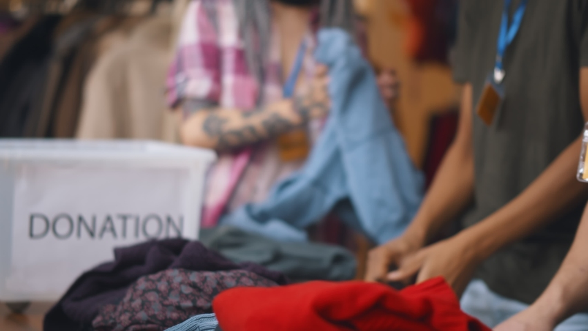 Close up of volunteers sorting donated clothes in charity shop. Team of workers unpacking boxes with clothes in second hand store. Charity and donation concept Royalty-Free Stock Footage #1063780618