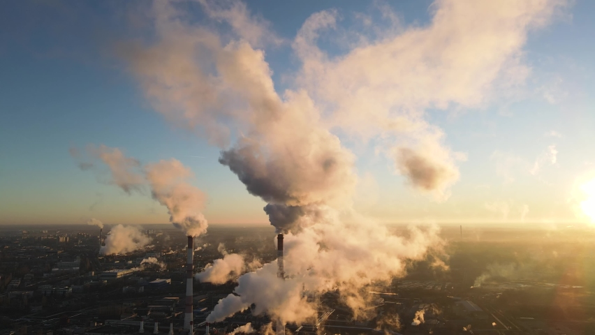 Aerial view of high smoke stack with smoke emission. Plant pipes pollute atmosphere. Industrial factory pollution, smokestack exhaust gases. Industry zone, thick smoke plumes. Climate change, ecology