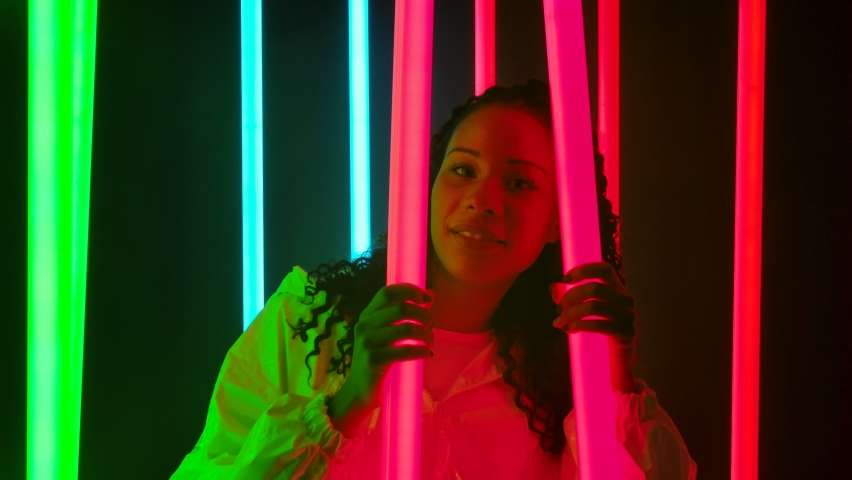 Portrait of a young lovely female African American with long curly hair poses against a dark studio with bright multicolored neon lights. Slow motion. Close up.