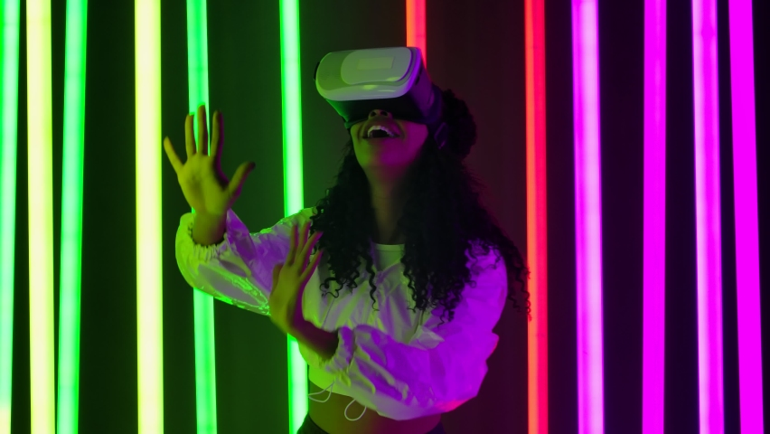 Portrait of a young lovely female African American with virtual reality goggles. Slow motion.