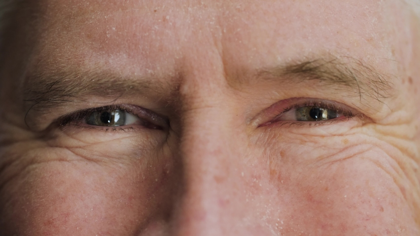 Face of happy elderly middle aged man smiling with friendly blue eyes. Handsome mature male senior citizen with wrinkles on attractive face looking and laughing at camera. Macro extreme close up, 4K.