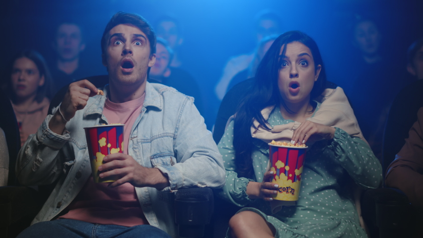 Young people watching film in dark hall. Attractive couple surprising in movie theater. Worried friends sitting with popcorn in cinema. Two friends spending date in cinema. Royalty-Free Stock Footage #1063803385