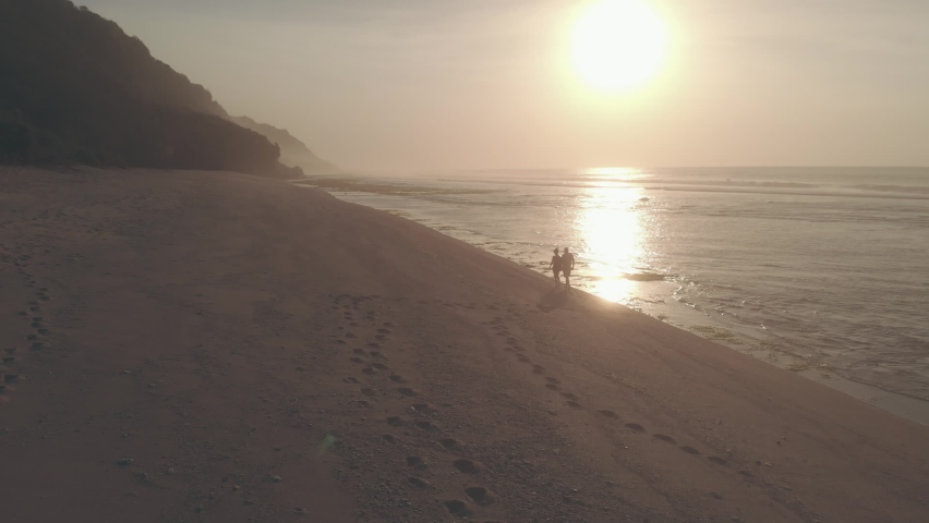 Drone aerial view. Silhouettes of couple in love walking on the beach at sunset. Man and woman holding hands walk, leaving footprints on sand. Sun reflecting in the sea. Concept of romance and love