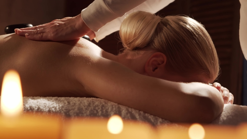 Young and beautiful woman gets hot stone massage therapy in the spa salon. Healthy lifestyle and body care concept. Royalty-Free Stock Footage #1063817527