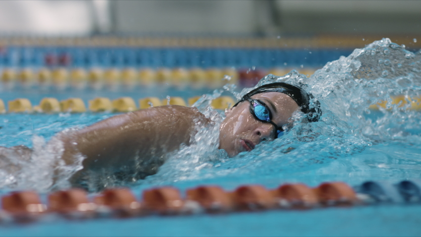 Young female swimmer performing front crawl technique. Sport and endurance theme. Camera moving with woman swimmer. Royalty-Free Stock Footage #1063818469