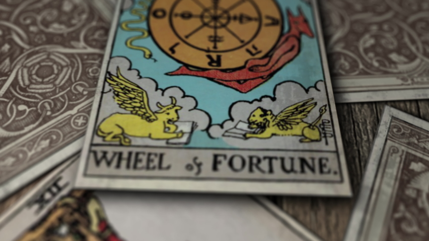 Tarot cards falling on a wooden table. One of the cards is revealed and it says wheel of fortune, with a compass in the middle and different figures of creatures with wings. Mystic game. Close up | Shutterstock HD Video #1063830244