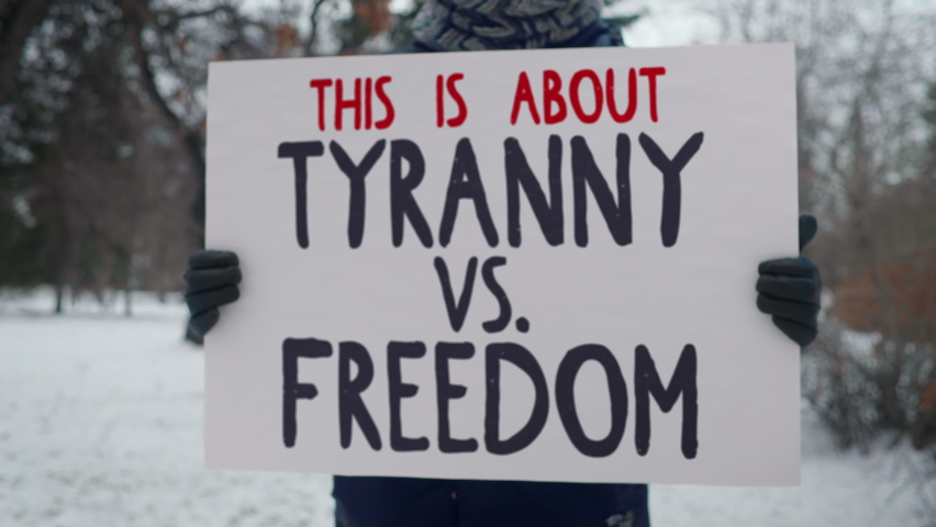 Political protest in a cold winter park. A person is holding up a sign with words This is about Tyranny vs. Freedom. Advocating for human rights. Drawing attention to unjust laws and regulations. Royalty-Free Stock Footage #1063830247