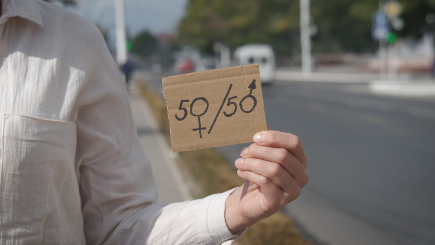 50 to 50. Equality of women. A woman in the city holding a 50-50 sign.