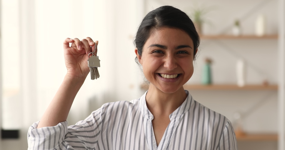 Head shot of Indian female showing keys from new apartment. Happy homeowner portrait, real estate agent selling property. Housing improvement, bank loan and modern house purchase, insurance concept Royalty-Free Stock Footage #1063839028