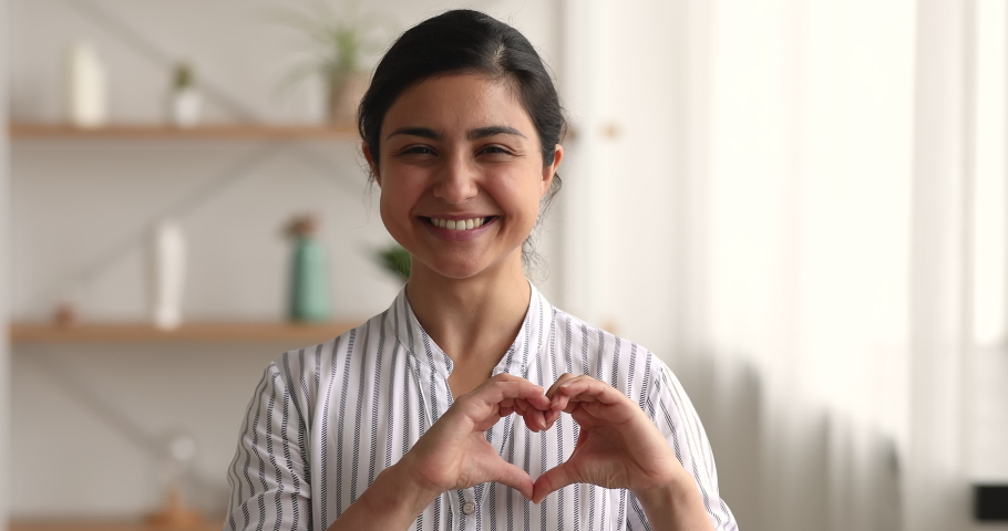 Headshot portrait 25s Indian woman show heart sign make symbol with hands feels grateful smile looks at camera standing indoors. Love support demonstration, volunteering, donation, good deed concept Royalty-Free Stock Footage #1063839259