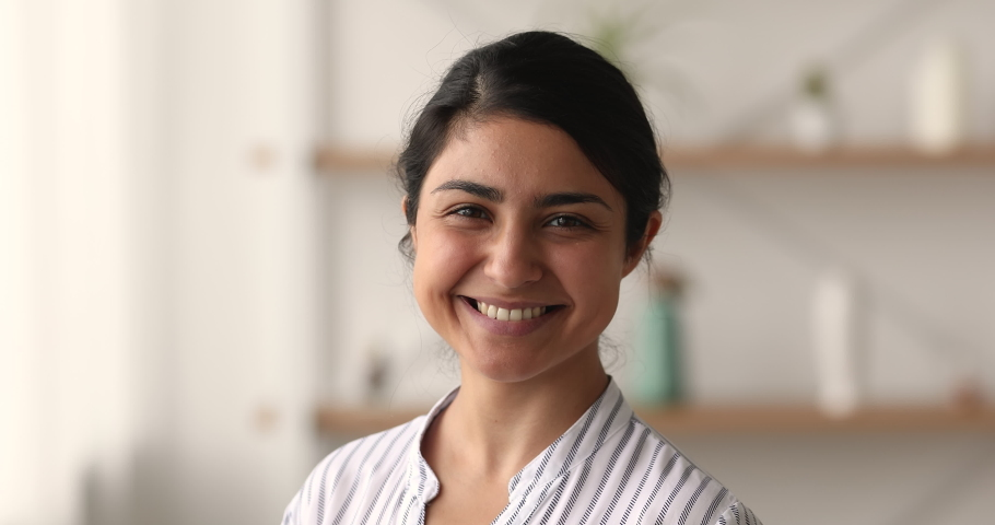 Head shot close up happy beautiful 30s Indian female pose indoor smile looking at camera. Dental services satisfied client, professional occupation person, tutor, blogger, freelancer portrait concept | Shutterstock HD Video #1063839310