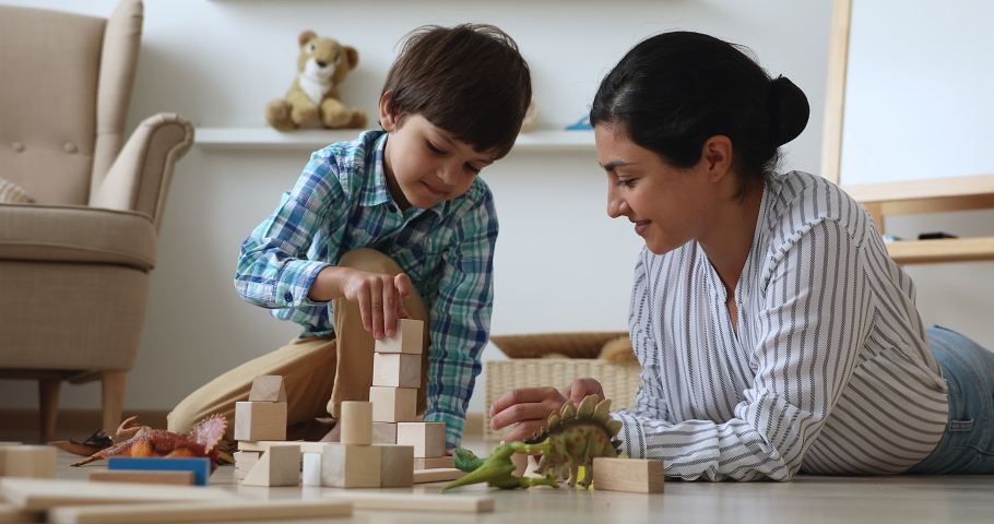 Indian nanny spend time in modern cozy home with little boy. Loving caring mother play with preschooler son with dinosaurs, construct tower use wooden bricks set. Child development, playtime concept Royalty-Free Stock Footage #1063839394