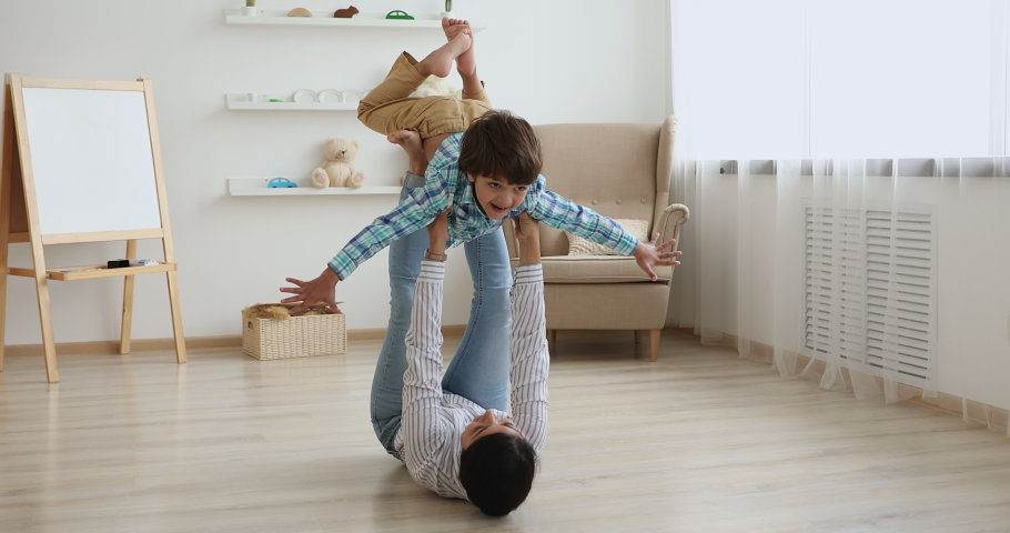 Indian woman play with little son while lying on warm wooden floor in living room lifting up happy kid boy, child looks like fly in air pretends a plane dream together about family travel, fun concept