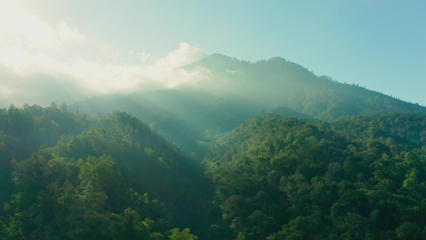 Foggy landscape tropical rain forest jungle island Bali on background majestic volcano Gunung Agung or Mount Agung, located in the district of Karangasem. 4K Aerial view Royalty-Free Stock Footage #1063840099