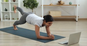 Indian young slim woman watch video on laptop perform butt workout plank leg raises on mat. Fitness for weight loss, burn gluteus muscles, improve shape. Sport from home using on-line training concept