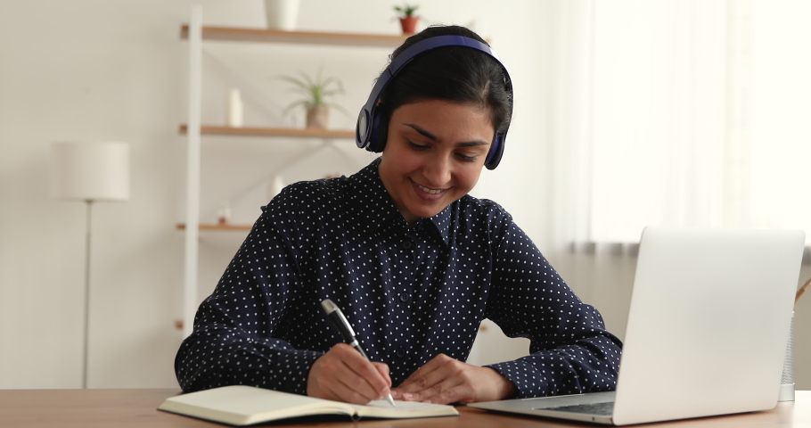 Beautiful Indian woman sit at desk using laptop listen audio course through wireless headphones makes notes on copybook enjoy language learning, develop knowledge. Self-education, e-learning concept