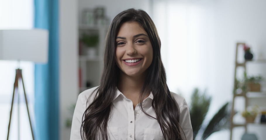 Slow motion of beautiful smiling confident young caucasian woman looking at camera smiling in living room or home office. Happy millennial authentic real girl close up front portrait.