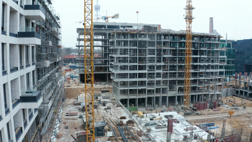 Aerial Flight Over a New Constructions Development Site. Urban Construction Site, Aerial View.  High crane works on building site. Crane and building construction site.  Royalty-Free Stock Footage #1063853677