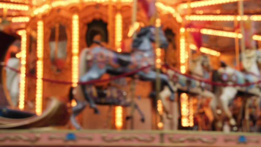 Blurry background carousel with horses lots of golden lights in the evening. a holiday concept with kids or romantic Valentine's Day outing. Carousel vintage on the square Royalty-Free Stock Footage #1063862527