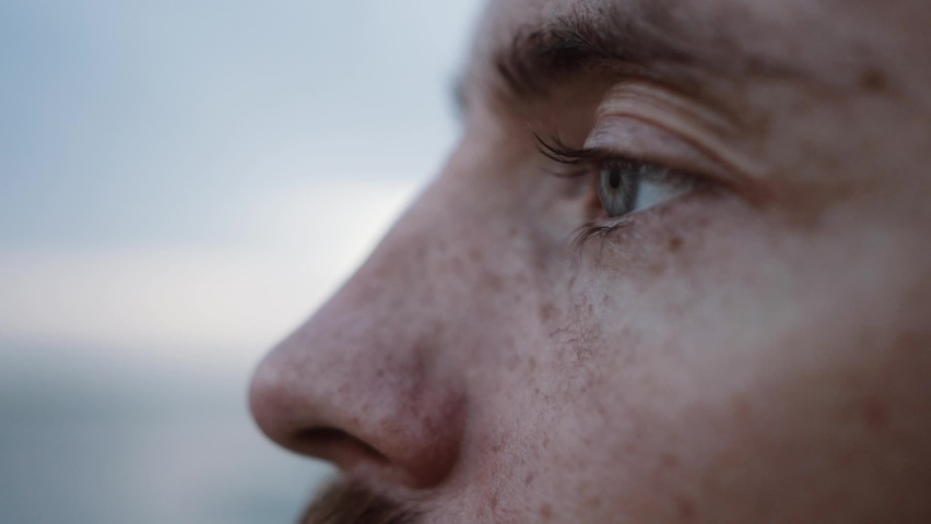 Male look, a young man with a beard opens his eyes, gray eyes, looks straight and closes his eyes, on a blurred background, close-up, slow-motion