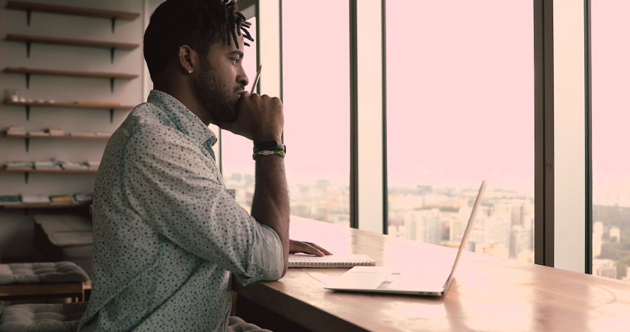 Concentrated african 35s manager working on laptop sit in modern office. Employee think of business issues, search solution, do on-line financial market research, creative telework, brainwork concept Royalty-Free Stock Footage #1063885462