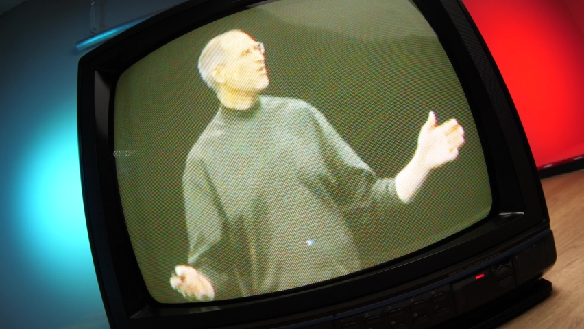Apple Steve Jobs presenting the new iPhone device on an old CRT television. 00s era technology MONTREAL CANADA DECEMBER 2020