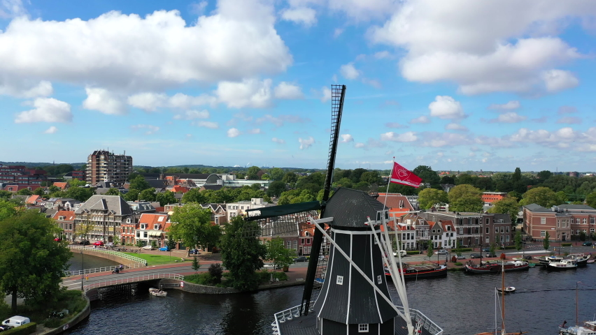 Aerial view on a small town and a traditional Dutch windmill in the front. Haarlem, Netherlands. Filming from the air with a drone in 4K.  Royalty-Free Stock Footage #1063889401