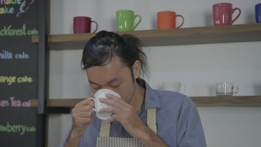 Coffee shop concept of 4k Resolution. An Asian male employee tasting coffee in the store.